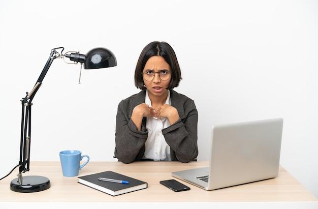 Junge geschäftsfrau mit gemischter abstammung, die im büro arbeitet und auf sich selbst zeigt