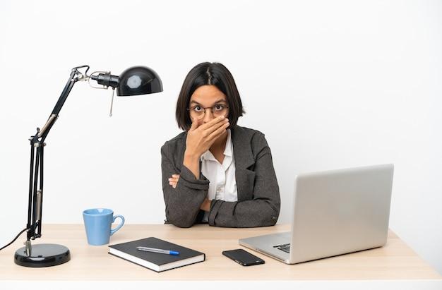 Junge geschäftsfrau mit gemischter abstammung, die im büro arbeitet und den mund mit der hand bedeckt