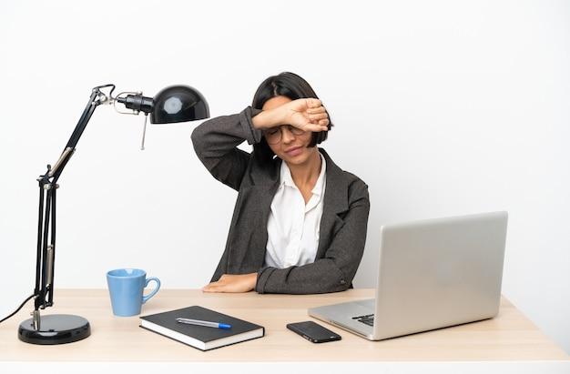 Junge geschäftsfrau mit gemischter abstammung, die im büro arbeitet und die augen mit den händen bedeckt?