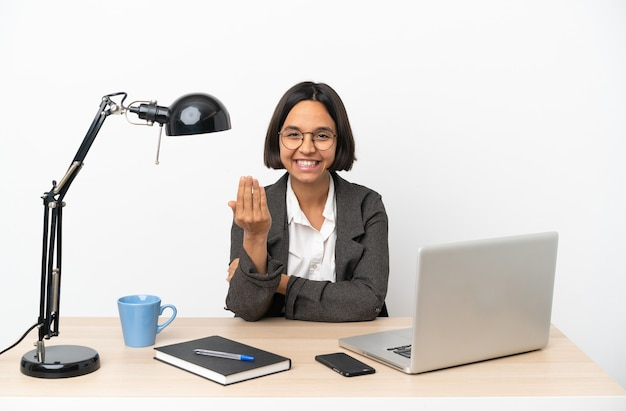Junge geschäftsfrau mit gemischter abstammung, die im büro arbeitet und einlädt, mit der hand zu kommen. schön, dass du gekommen bist