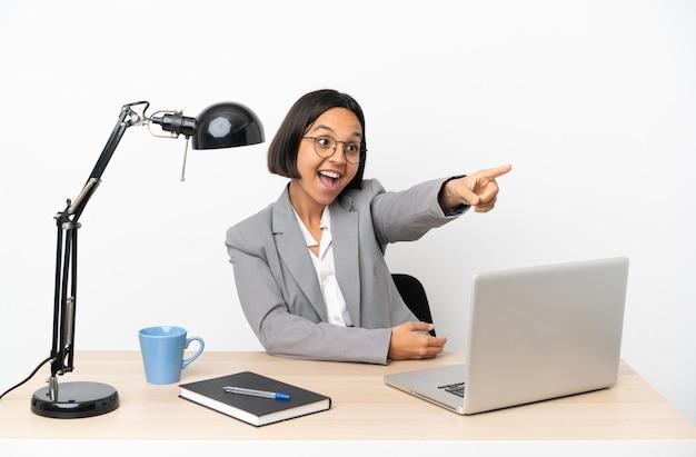 Junge geschäftsfrau mit gemischter abstammung, die im büro arbeitet und wegzeigt
