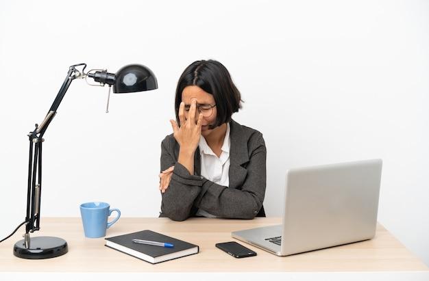 Junge geschäftsfrau mit gemischter abstammung, die im büro mit kopfschmerzen arbeitet working