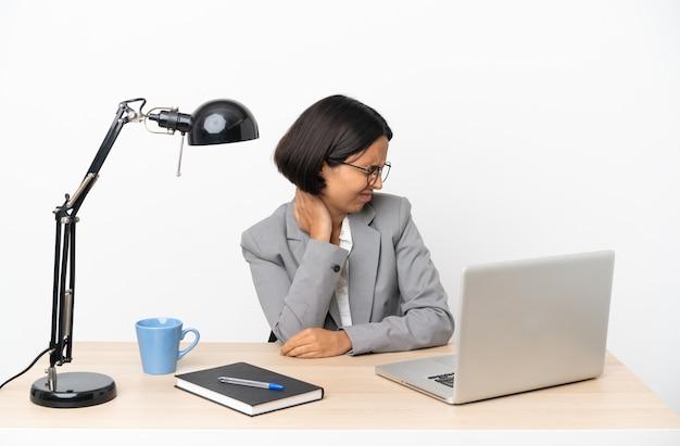 Junge geschäftsfrau mit gemischter abstammung, die im büro mit nackenschmerzen arbeitet with
