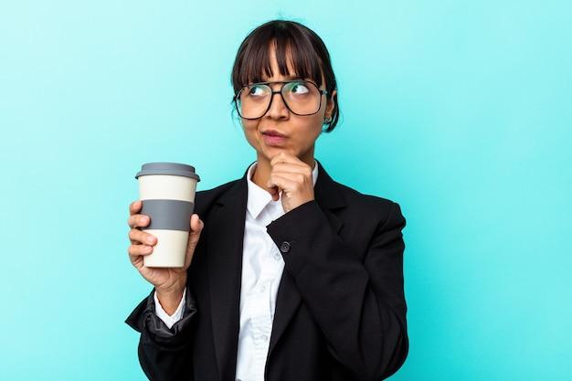 Junge geschäftsfrau mit gemischter rasse, die einen kaffee auf blauem hintergrund isoliert hält und seitlich mit zweifelhaftem und skeptischem ausdruck schaut