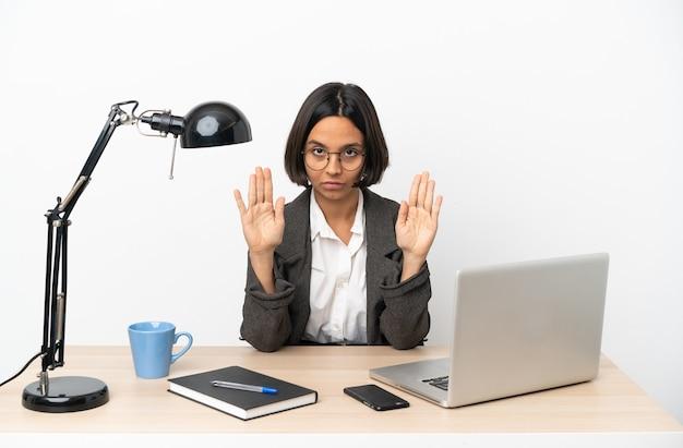 Junge geschäftsfrau mit gemischter rasse, die im büro arbeitet, stoppgeste macht und enttäuscht ist
