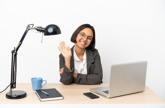Junge geschäftsfrau mit gemischter rasse, die im büro arbeitet und mit der hand mit glücklichem ausdruck grüßt