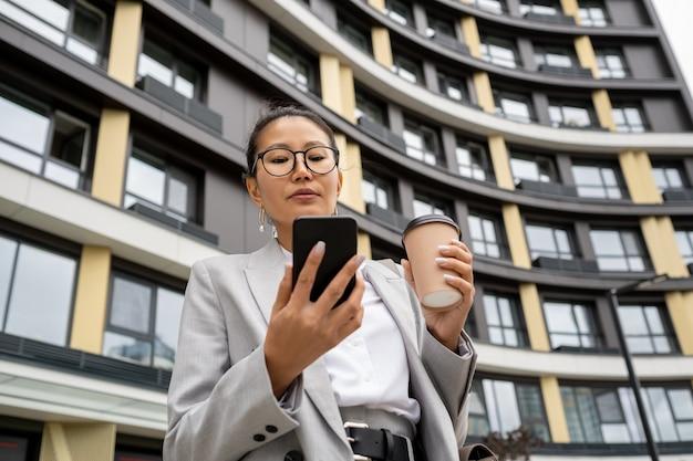 Junge geschäftsfrau mit getränk-sms im smartphone