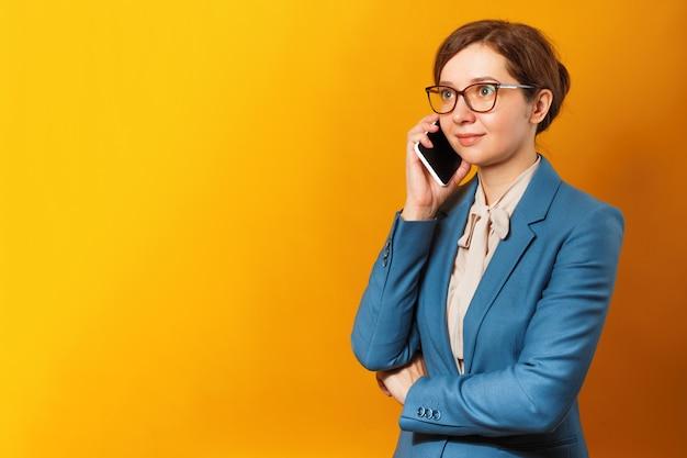 Junge geschäftsfrau mit gläsern und einer klage sprechend an einem handy