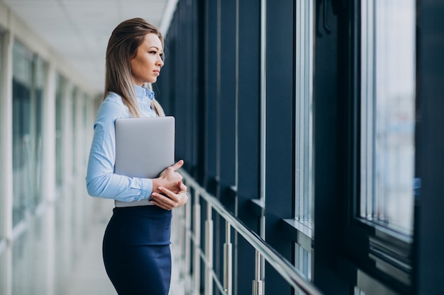 Junge geschäftsfrau mit laptop, der in einem büro steht