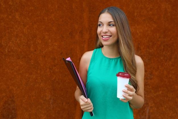 Junge geschäftsfrau mit ordnern und kaffee, die zur seite mit kopienraum auf rosthintergrund schauen.