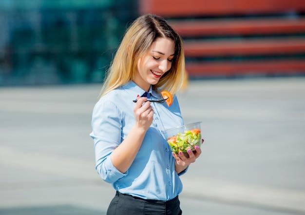 Junge geschäftsfrau mit salatbrotdose auf im freien