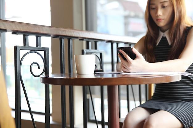 Junge geschäftsfrau mit smartphone und kaffee