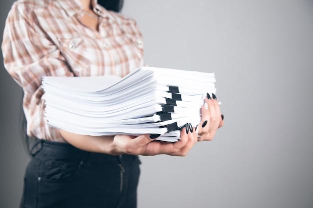 Junge geschäftsfrau mit stapel papieren