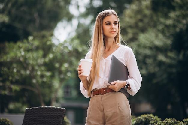 Junge geschäftsfrau mit trinkendem kaffee des laptops außerhalb des cafés