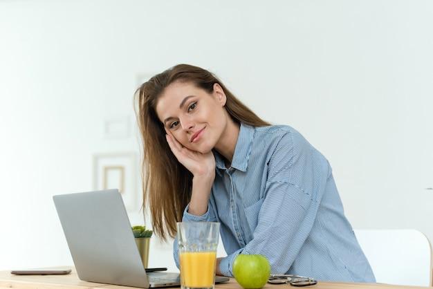 Junge geschäftsfrau oder studentin, die zu hause am esstisch sitzt, mit ihrem laptop und papierkram nachdenklich starrt und in die kamera schaut.