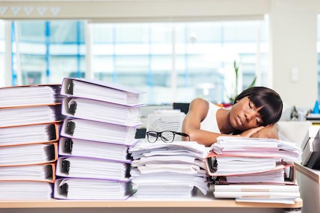 Junge geschäftsfrau schläft auf den papieren im büro