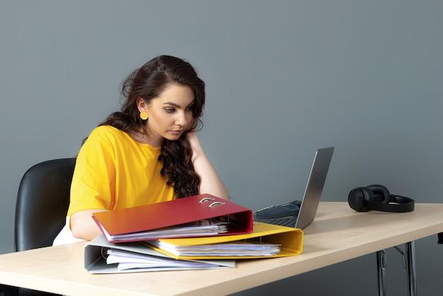 Junge geschäftsfrau sitzt am tisch und arbeitet mit dokumenten und laptop, isoliert auf grauem hintergrund