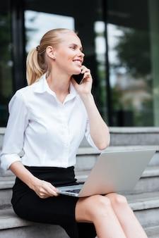 Junge geschäftsfrau sitzt auf der treppe und telefoniert draußen mit dem handy