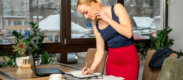 Junge geschäftsfrau spricht am telefon und schreibt notizen, die im büro oder im café stehen