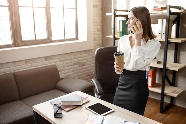 Junge geschäftsfrau stehen am tisch im zimmer. sie telefoniert und schaut zum fenster. modell halten tasse kaffee.