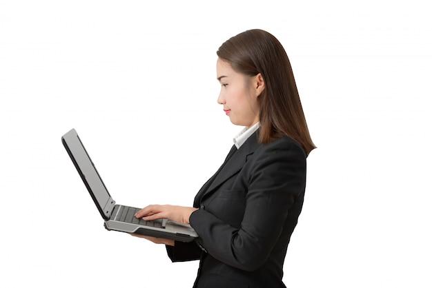 Junge geschäftsfrau, stehend, ein weißes hemd und einen schwarzen anzug tragend, die einen laptop-pc halten.