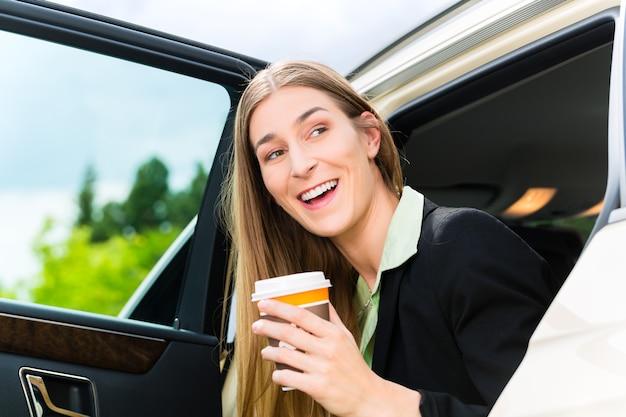 Junge geschäftsfrau steigt aus dem taxi, sie hält eine tasse kaffee