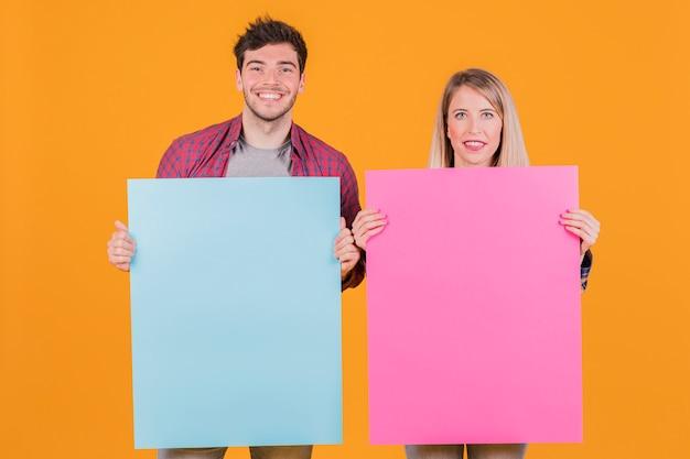 Junge geschäftsfrau und geschäftsmann, die blaues und rosa plakat gegen einen orange hintergrund hält