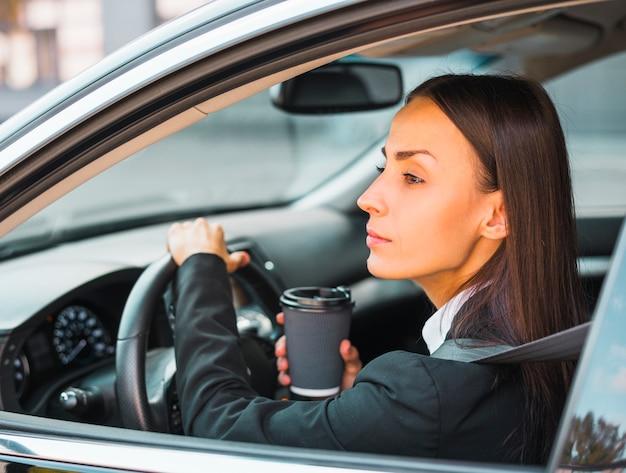 Junge geschäftsfrau, welche die wegwerfkaffeetasse fährt das auto hält