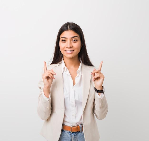 Junge geschäftsfrau zeigt mit beiden vorderfingern nach oben und zeigt ein leerzeichen