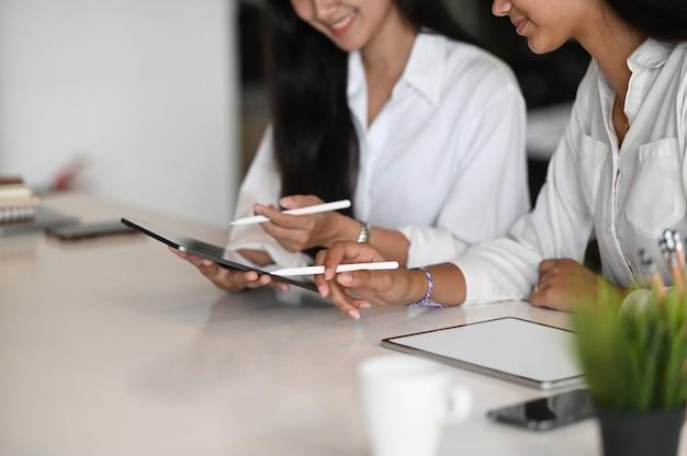 Junge geschäftsfrauen arbeiten ihre geschäftsstrategie zusammen mit digitalem tablet im modernen büro.