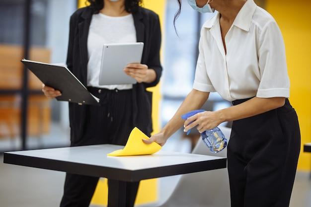 Junge geschäftsfrauen putzen den arbeitsplatz, wischen den schreibtisch mit gelbem lappen ab.