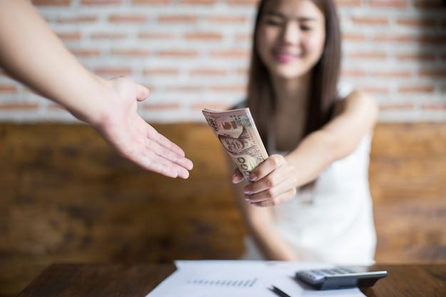 Junge geschäftsfrauen übermitteln ihren kunden banknoten zu den gewinnen, die die begünstigten erhalten sollen.