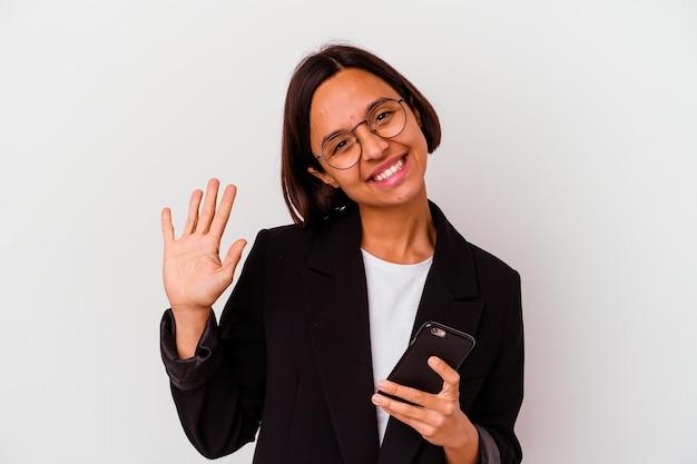 Junge geschäftsindianfrau, die ein telefon lokalisiertes lächelndes fröhliches zeigen nummer fünf mit fingern hält.