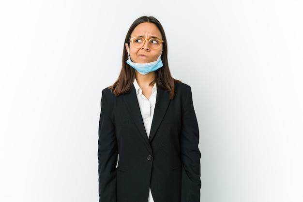 Junge geschäftslateinfrau, die eine maske trägt, um vor dem auf weißem hintergrund isolierten covid zu schützen, verwirrt, fühlt sich zweifelhaft und unsicher.