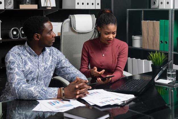 Junge geschäftsleute afroamerikanischer nationalität, die mit dokumenten und telefon arbeiten