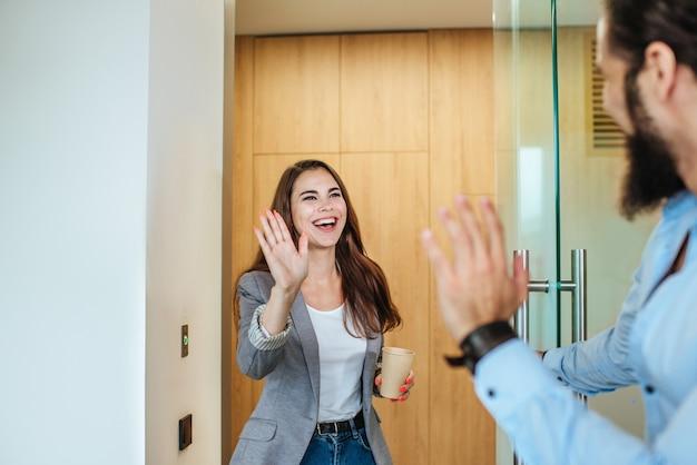 Junge geschäftsleute begrüßen sich im modernen büroarbeitsbereich