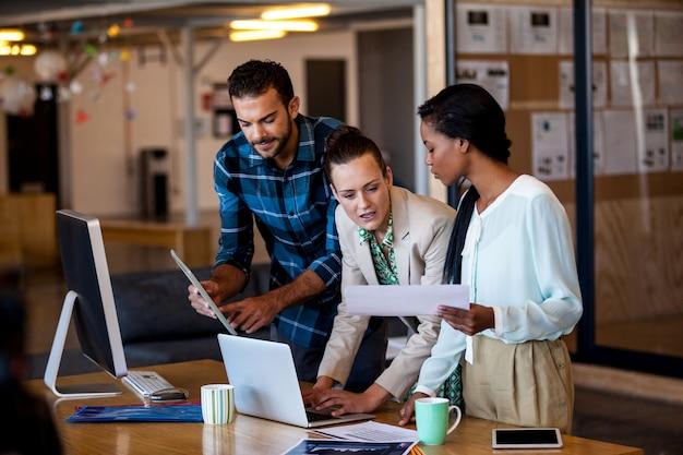 Junge geschäftsleute, die am computertisch arbeiten