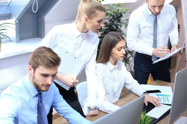 Junge geschäftsleute, die an ihren desktop-computern in den modernen büroräumen arbeiten.