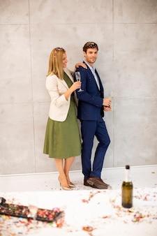 Junge geschäftsleute, die champagner im büro nach der weihnachtsfeier trinken