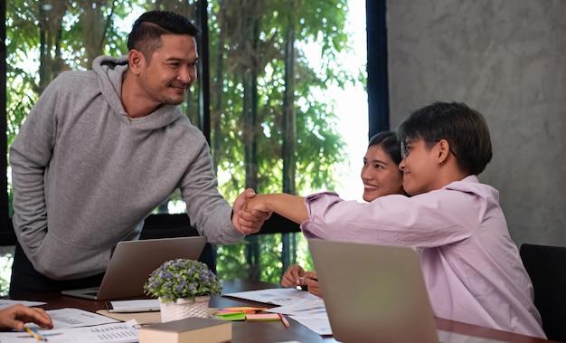 Junge geschäftsleute, die hand zusammen schütteln, mit glücklichem gefühl, teambesprechung des kollegen, erfolgsabkommen