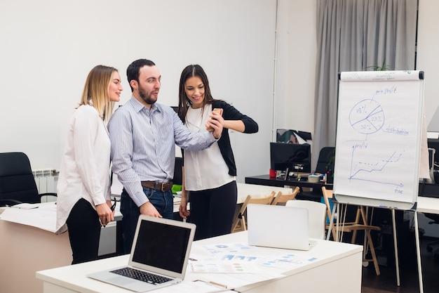 Junge geschäftsleute, die im büro während des treffens sitzen und mit papierkram unter verwendung von laptops diskutieren