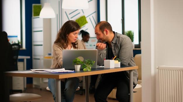 Junge geschäftsleute, die laptop verwenden, neue startup-idee zeigen, am schreibtisch im modernen firmenbüro sitzen. zwei kollegen arbeiten zusammen für innovatives produktdesign im kreativstudio.