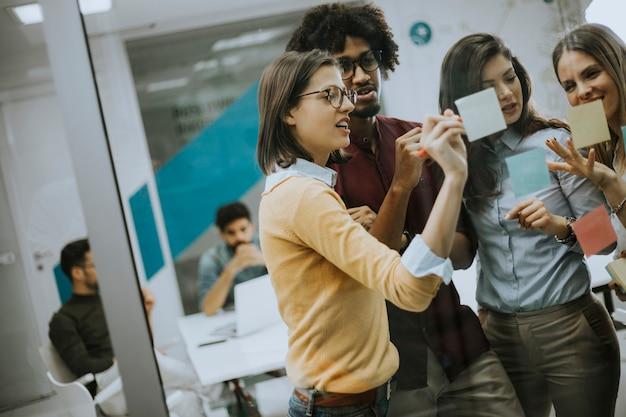 Junge geschäftsleute, die vor glaswand unter verwendung der post-itanmerkungen und -aufkleber sich besprechen