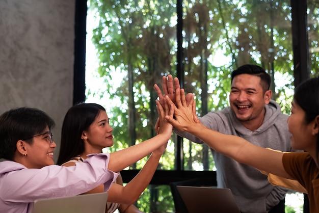 Junge geschäftsleute erreichen hände, die sich berühren. mit glücklichem gefühl. teamtreffen der kollegen, erfolgsabkommen