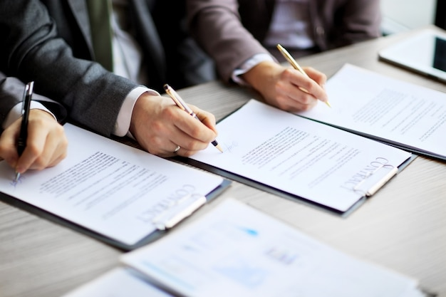 Junge geschäftsleute haben im vorstellungsgespräch einen arbeitsvertrag mit dem chef im büro unterschrieben