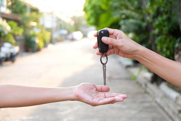Junge geschäftsleute reichen autoschlüssel bei ein