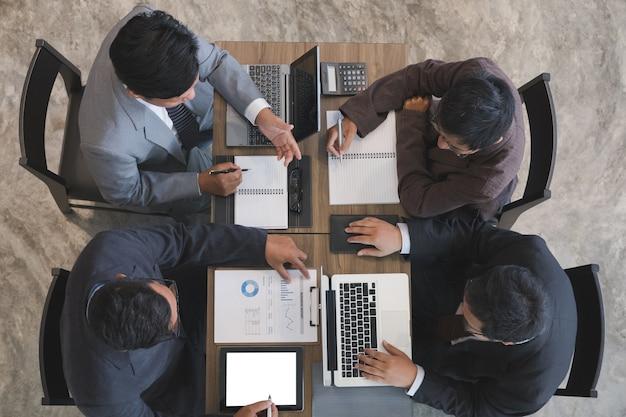 Junge geschäftsleute und unternehmer, die eine sitzung um tabelle im büro haben.