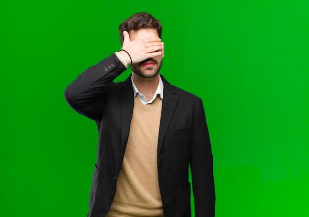 Junge geschäftsmannbedeckungsaugen mit einer hand, die erschrocken oder besorgt sich fühlt, blind auf eine überraschung gegen grüne wand sich wundert oder wartet