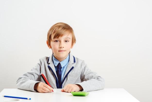Junge geschäftsmannkind im büro. netter schuljunge, der anzug und krawatte trägt. junge geschäftsjunge träumen vom zukünftigen beruf. bildungskonzept. neugründung für unternehmen.