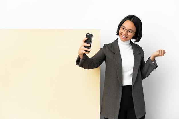 Junge geschäftsmischrassenfrau mit einem großen banner über isoliertem hintergrund, der ein selfie macht